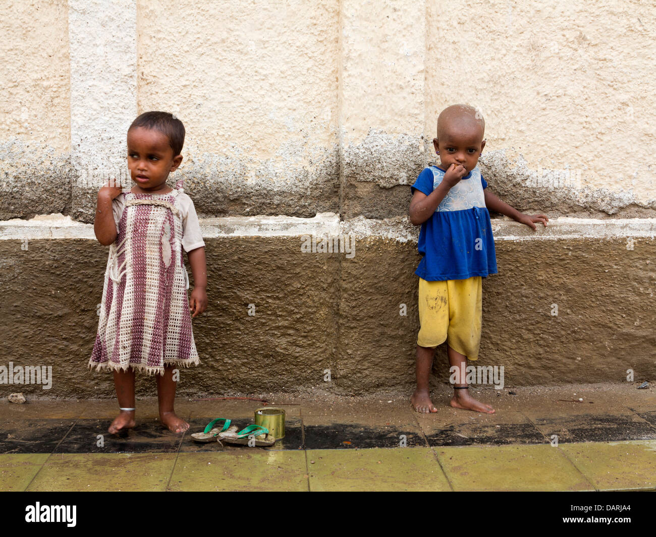 Africa, Eritrea, Massawa, Old Town, two young Eritrean children on wet pavement - Stock Image