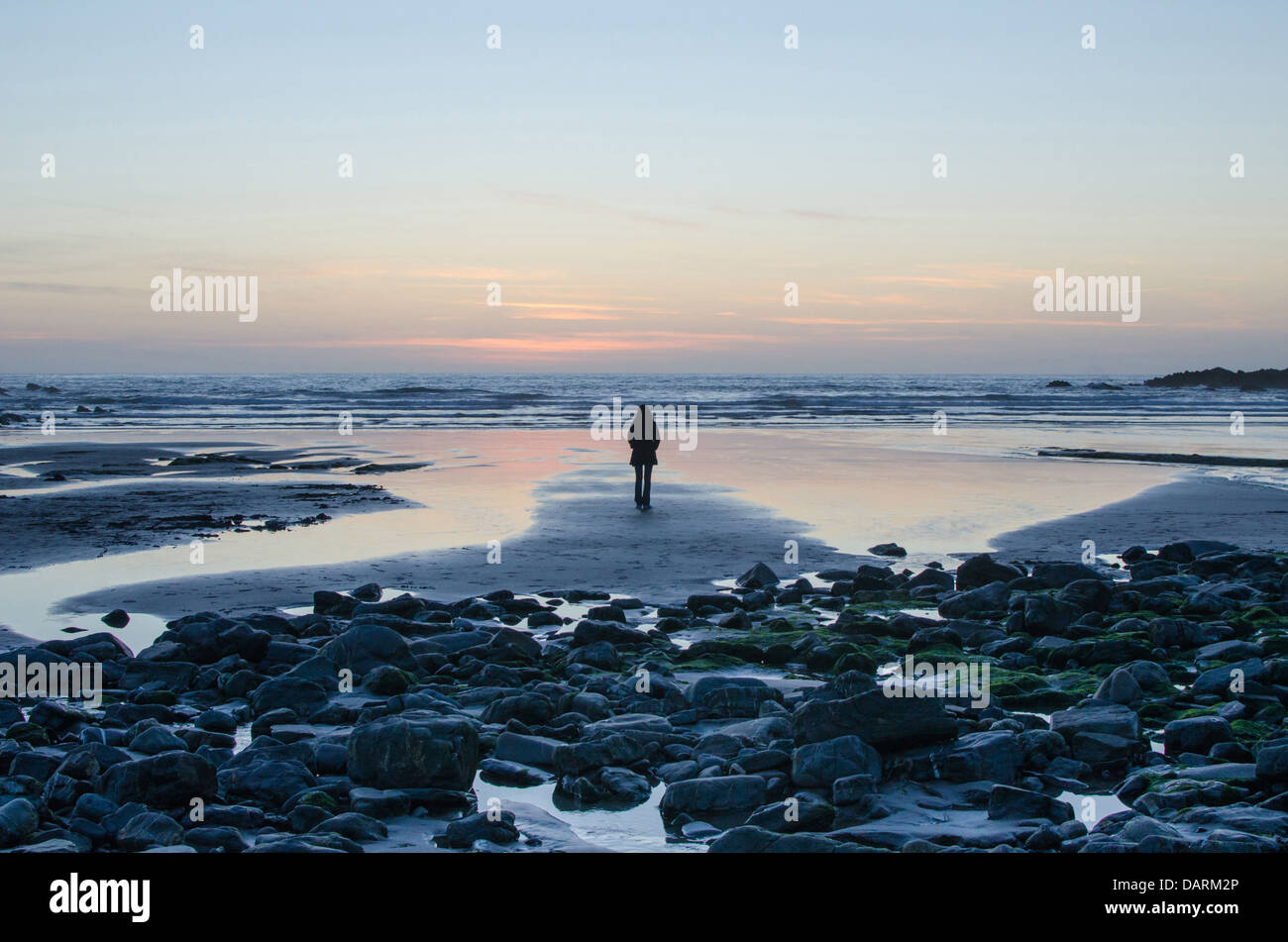A young woman looking out to sea during sunset at Crackington Haven, Cornwall, UK - Stock Image