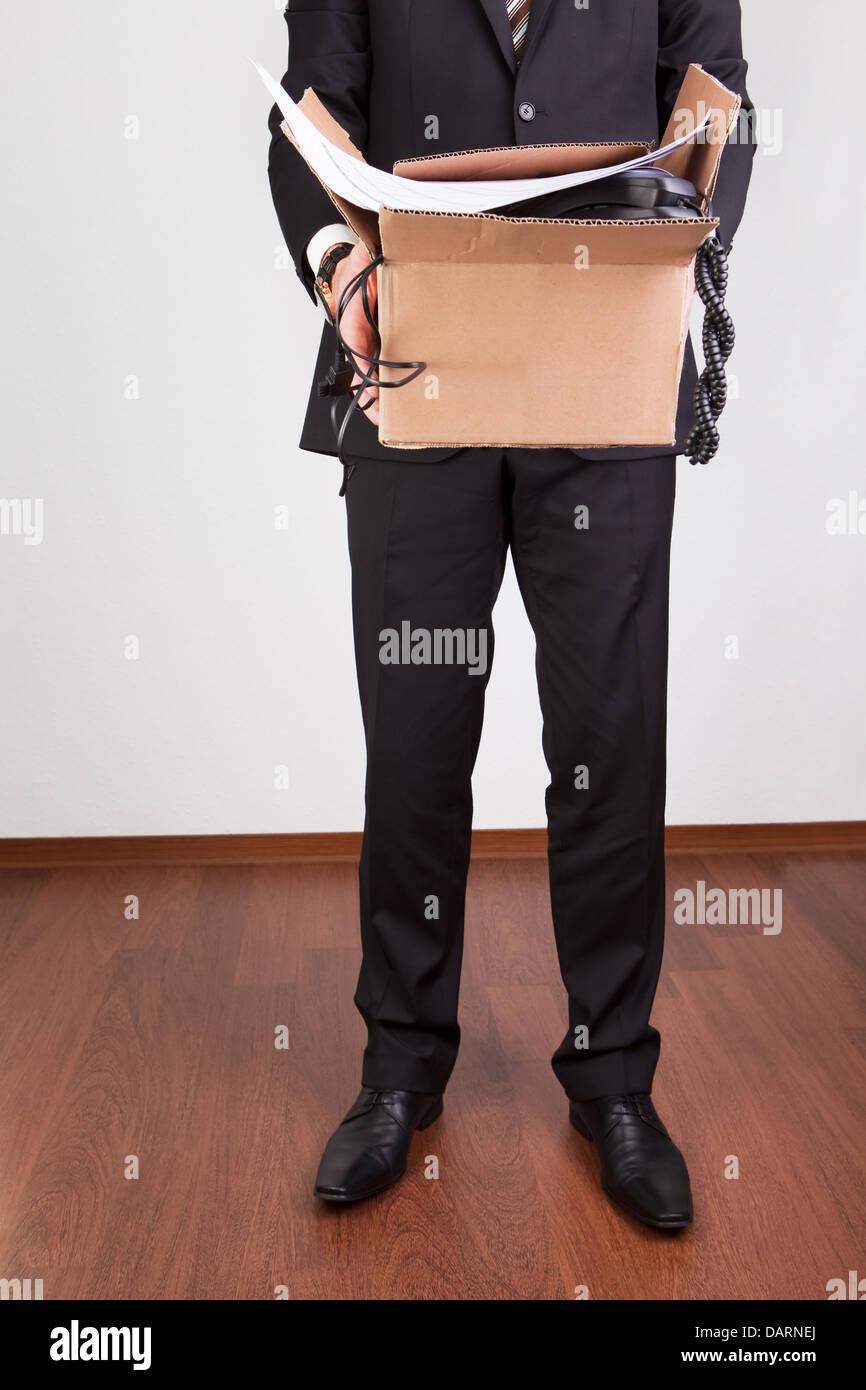 Downsized employee with belongings - Stock Image