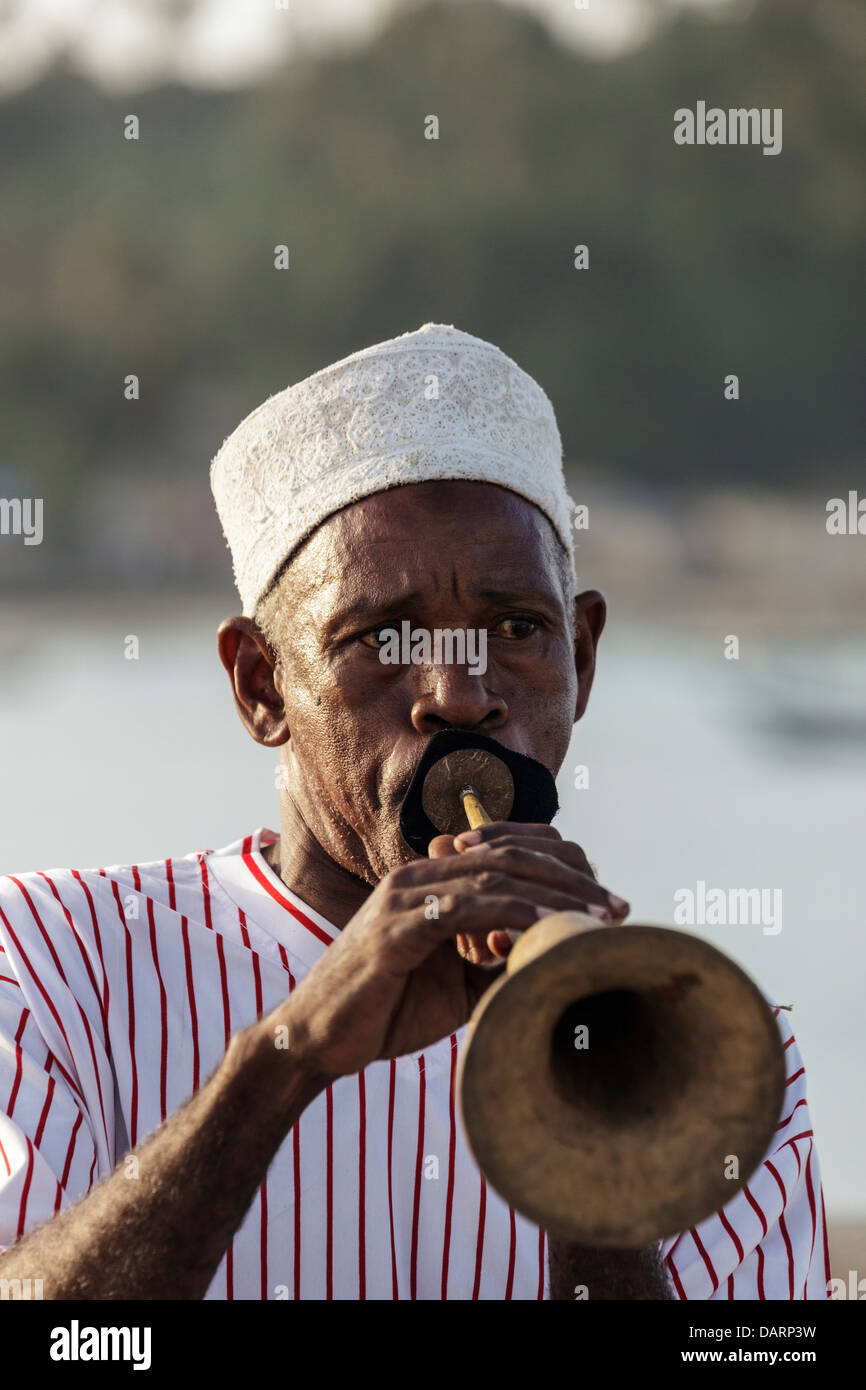 Africa, Tanzania, Zanzibar, Pemba Island. Man playing the zumari, a traditional horn instrument made of carved wood. - Stock Image