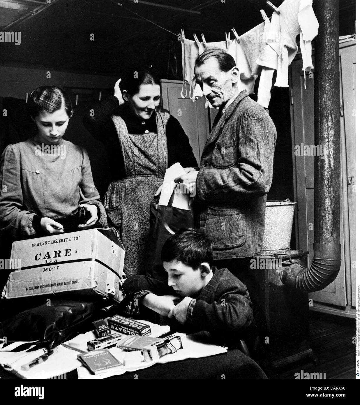 postwar period, CARE programme, German family unpacking a CARE Package, circa 1949, Additional-Rights-Clearences - Stock Image