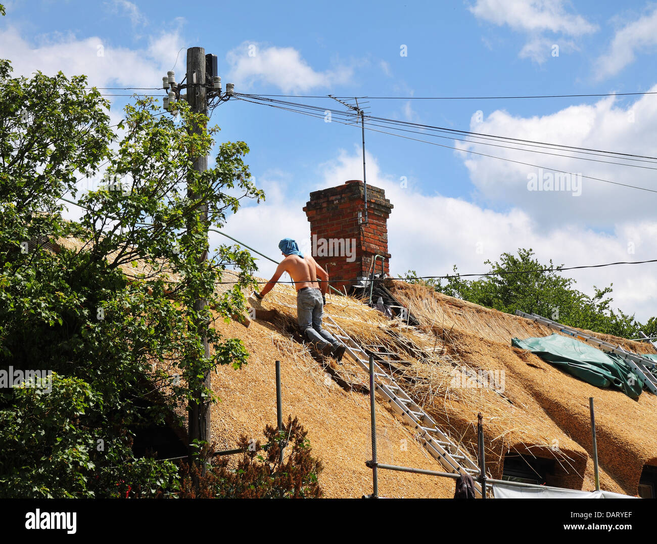 Man at work Thatching a cottage roof - Stock Image