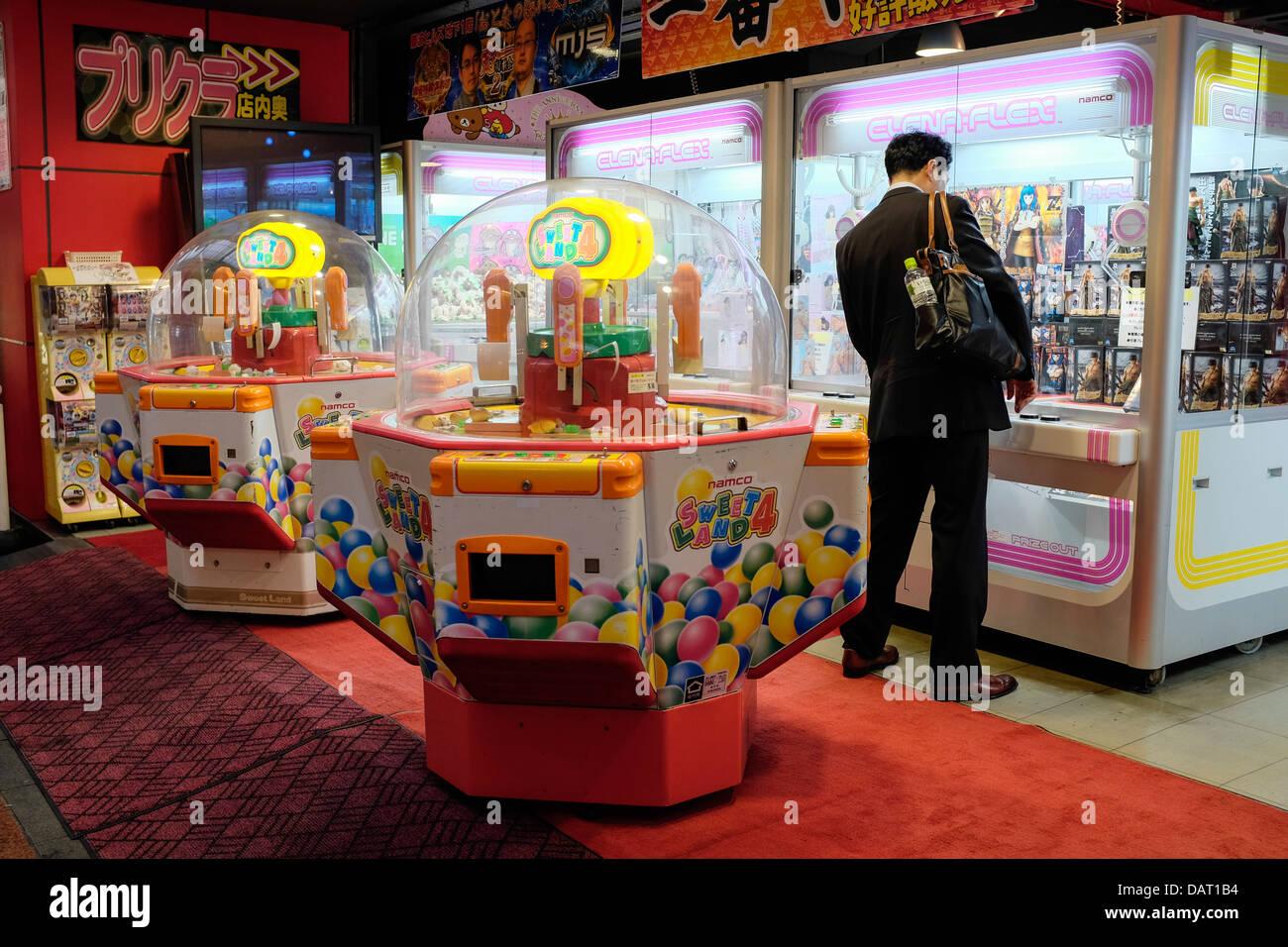 A Japanese Businessman playing an Arcade Claw Crane Game, Dotonburi, Osaka, Japan - Stock Image