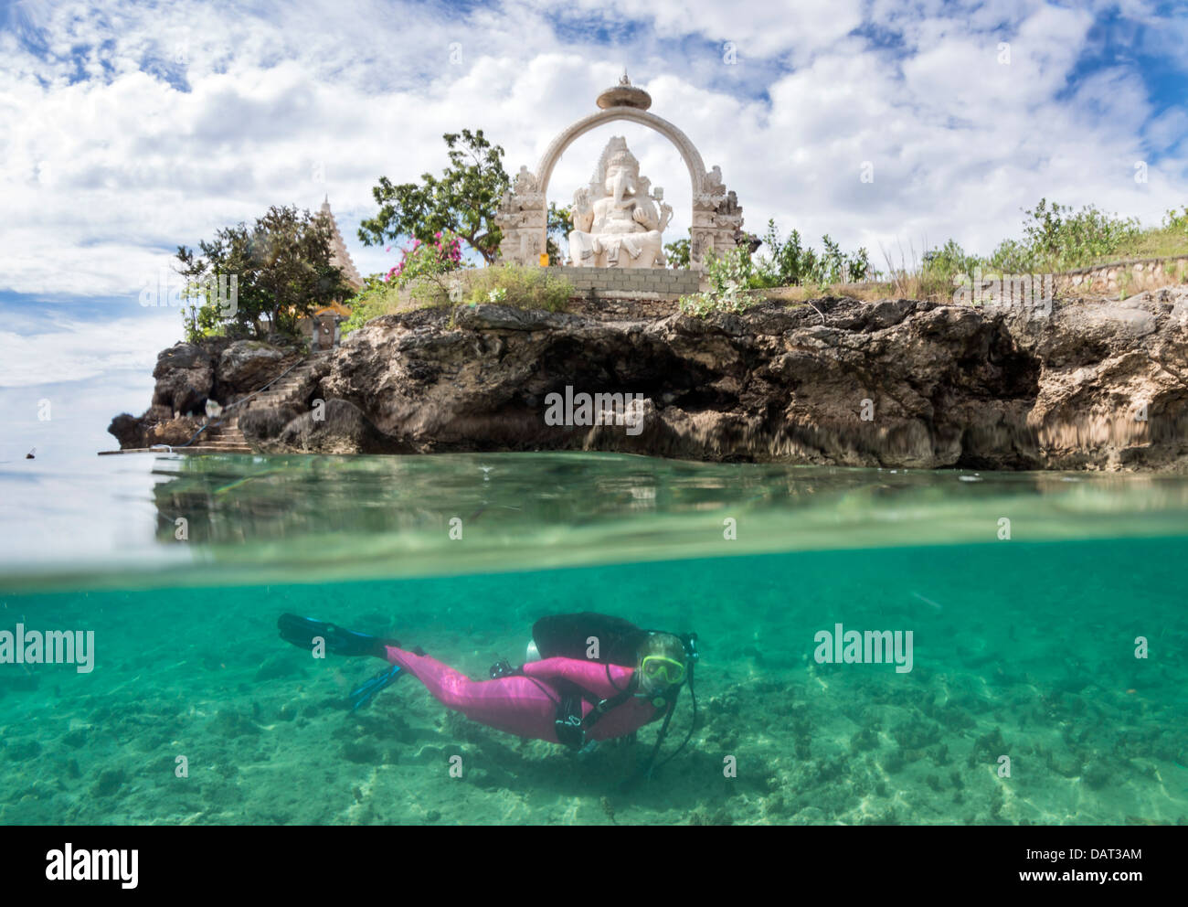 Split level view of blonde female diver exploring underwater alongside tropical island with temple in the background - Stock Image
