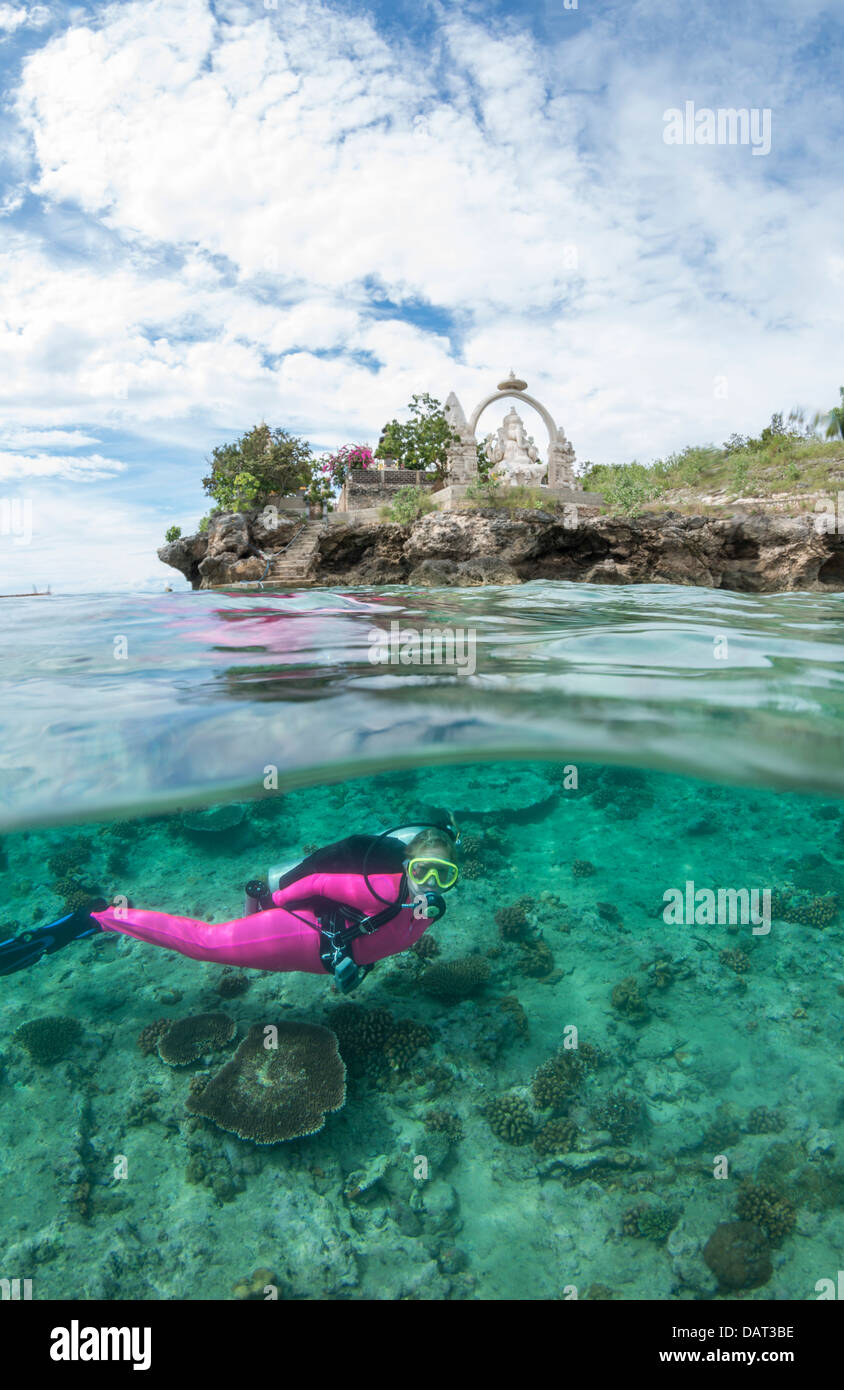 Split level view of blonde female diver exploring underwater alongside tropical island with Hindu temple in the - Stock Image