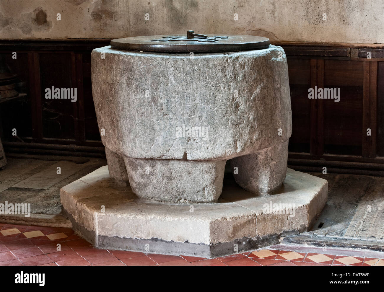 An old pre-Norman stone font dating from the 8th century (possibly an old standing stone) in the 15c St Stephen's Church, Old Radnor, Powys, Wales, UK Stock Photo
