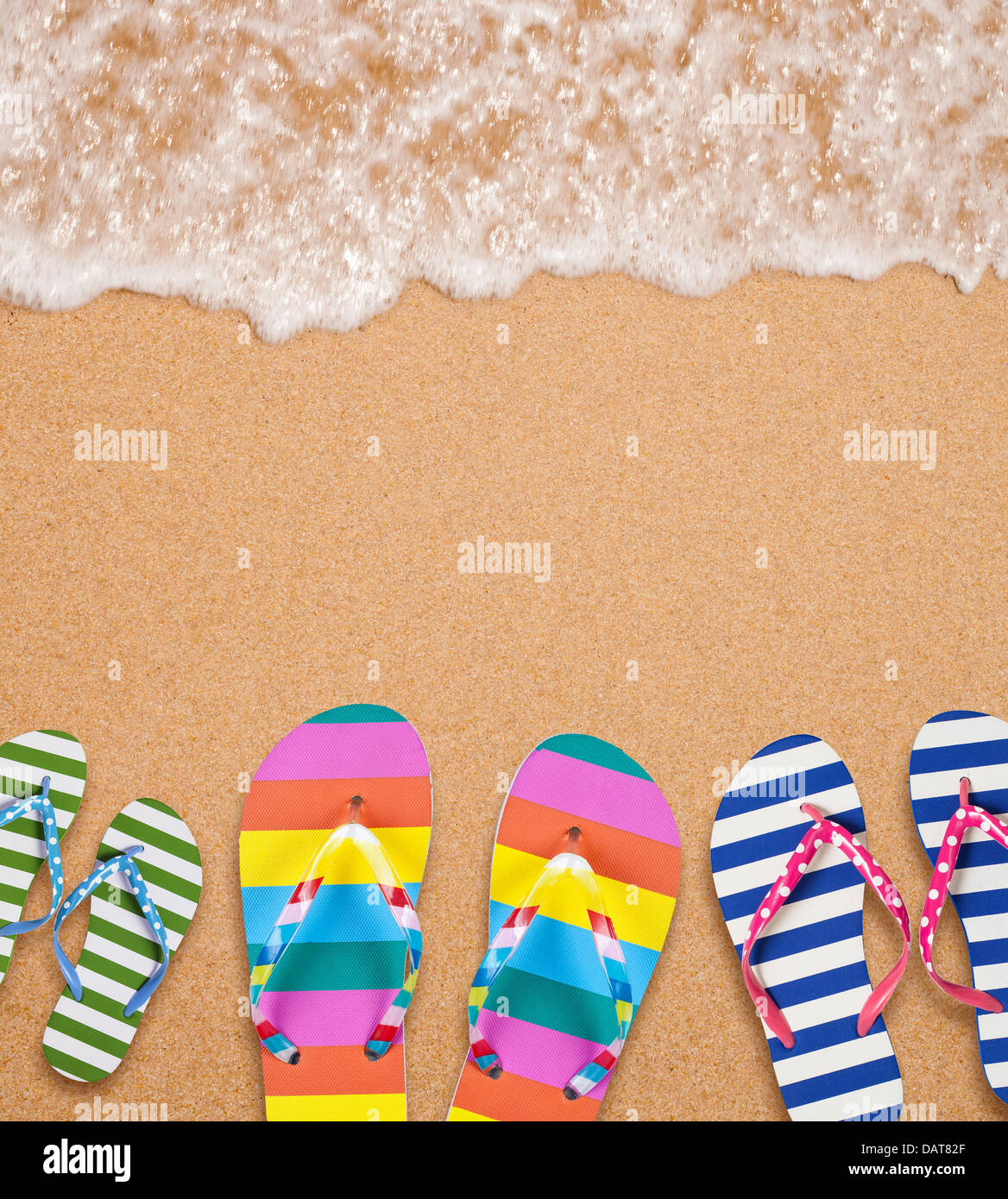 Family's flip flop pairs on sea surf with copy space for your text - Stock Image