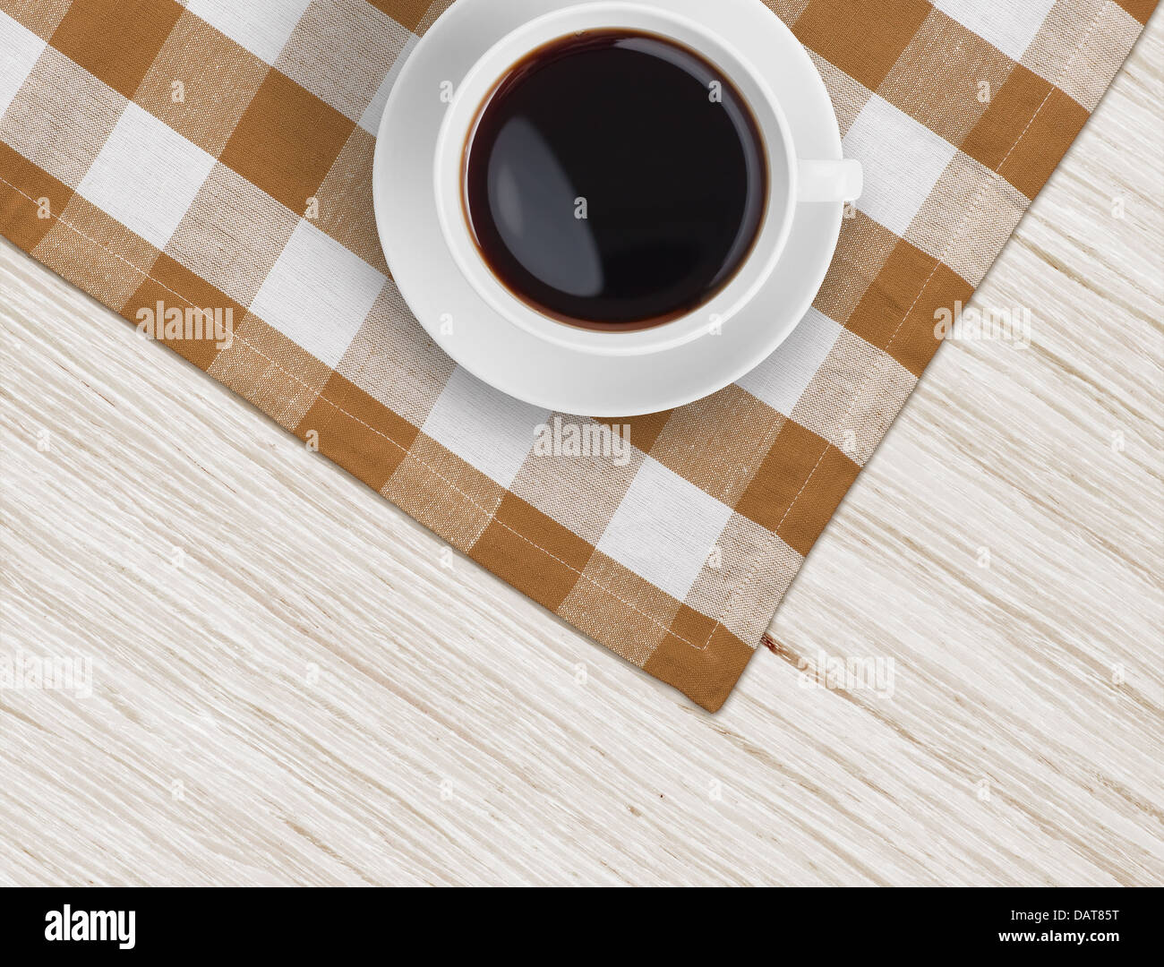 coffee cup top view on tablecloth over wooden table - Stock Image