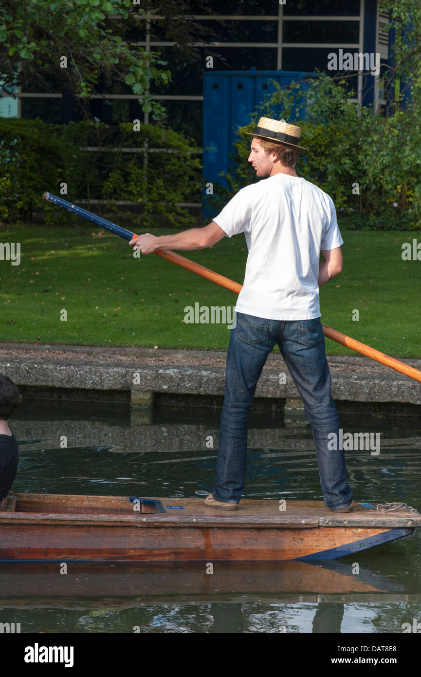 A young man standing on the back of a punt holding a punt pole punting in Cambridge wearing straw boater hat - Stock Image