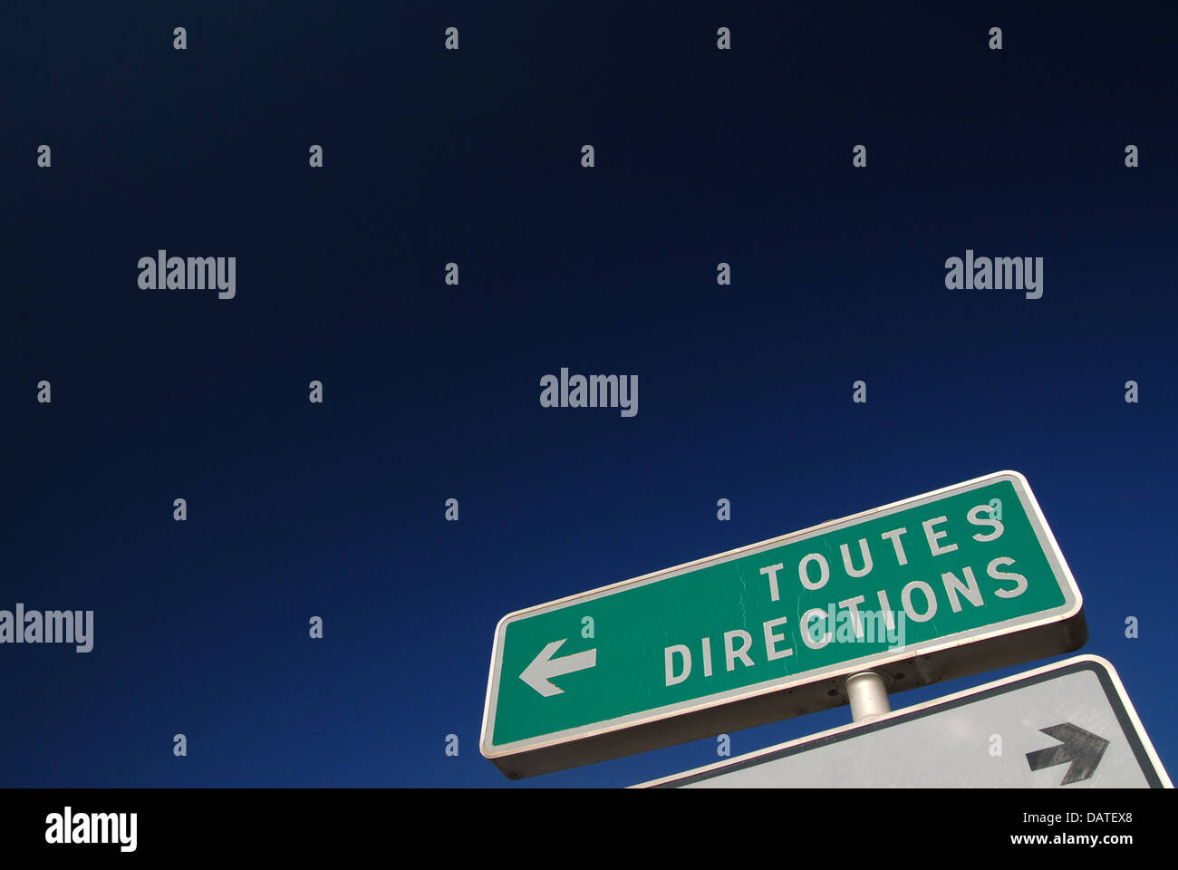 ALL DIRECTIONS / Toutes Directions. Road sign in France, against a deep blue sky. - Stock Image