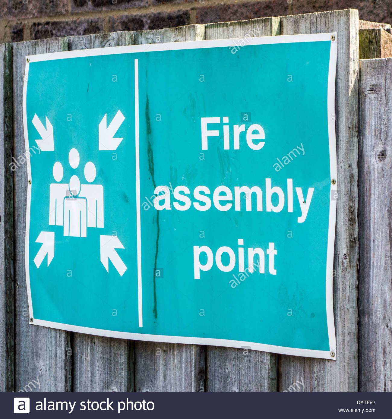 Fire assembly point sign on a wooden fence - Stock Image