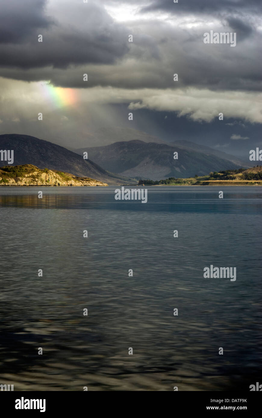 Storm clouds with rainbow over Loch Broom and the Highland mountains from Ullapool. Highlands, Scotland - Stock Image