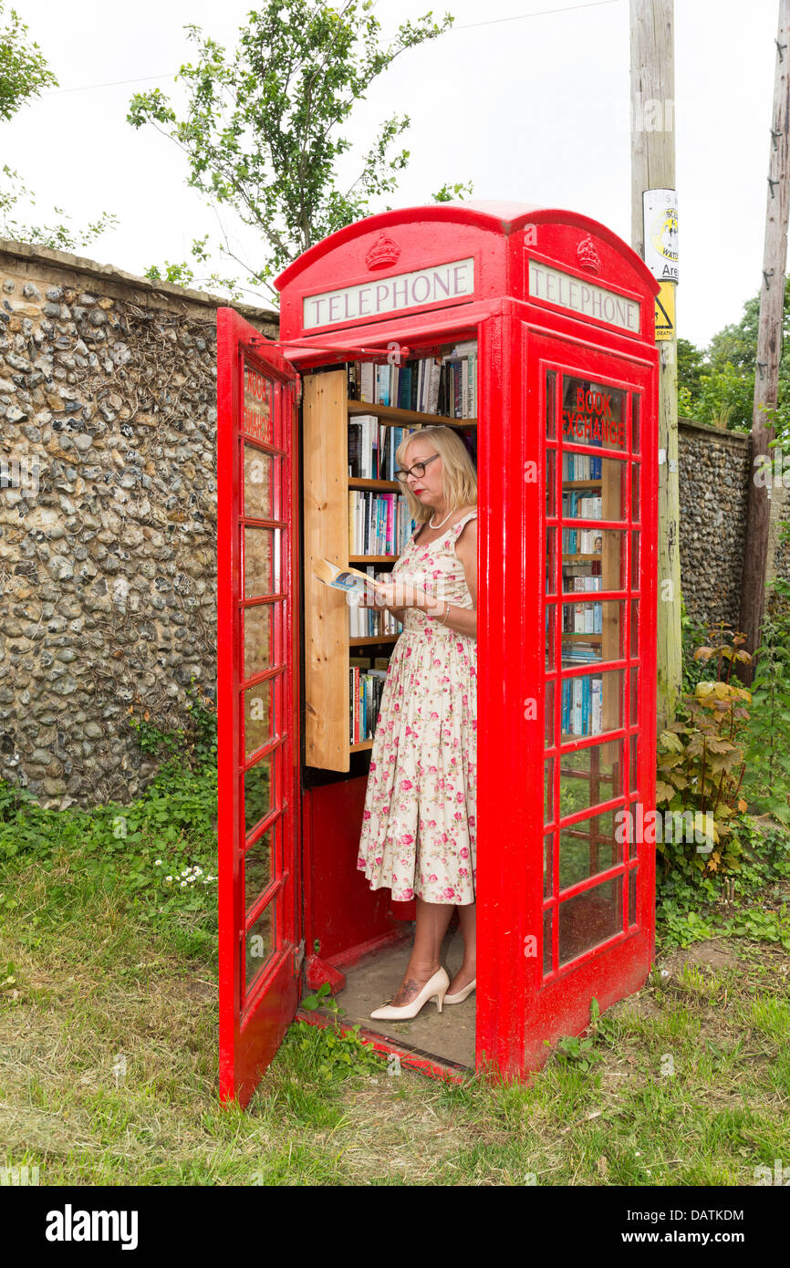 woman village library installed in disused red telephone box - Stock Image