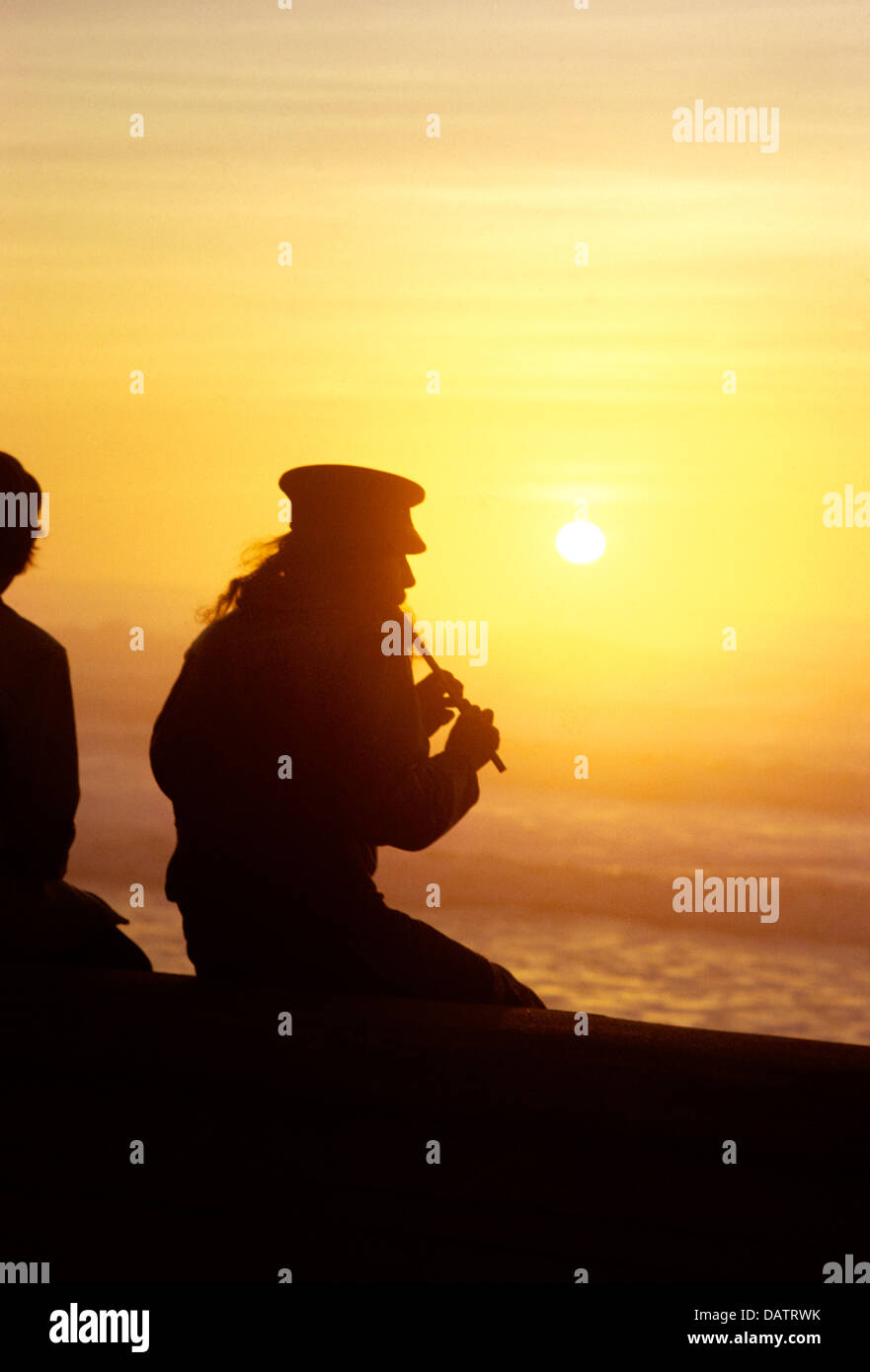 Hippie musician playing flute at sunset at San Francisco beach in sixties - Stock Image