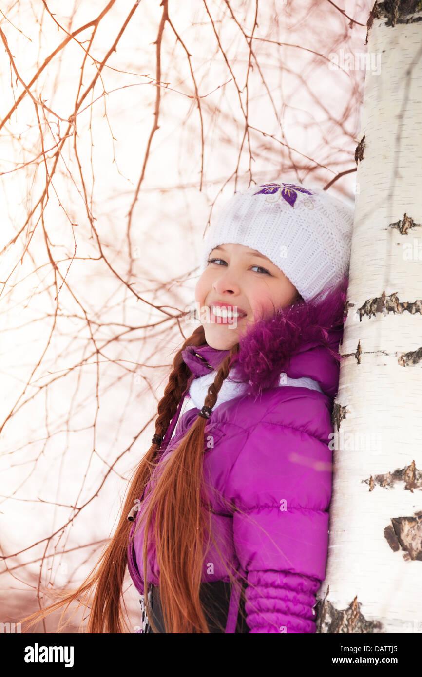 Cute little girl hugging he birch tree on winter snow day - Stock Image