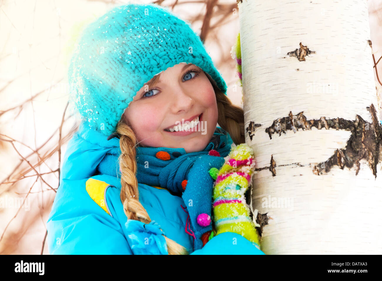 Portrait of little cute girl hiding behind the birch tree on winter snow day - Stock Image