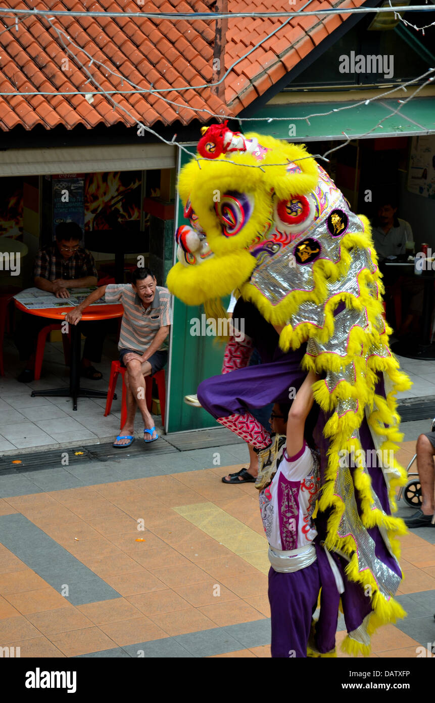 Man watches traditional Chinese Lion Dance - Stock Image