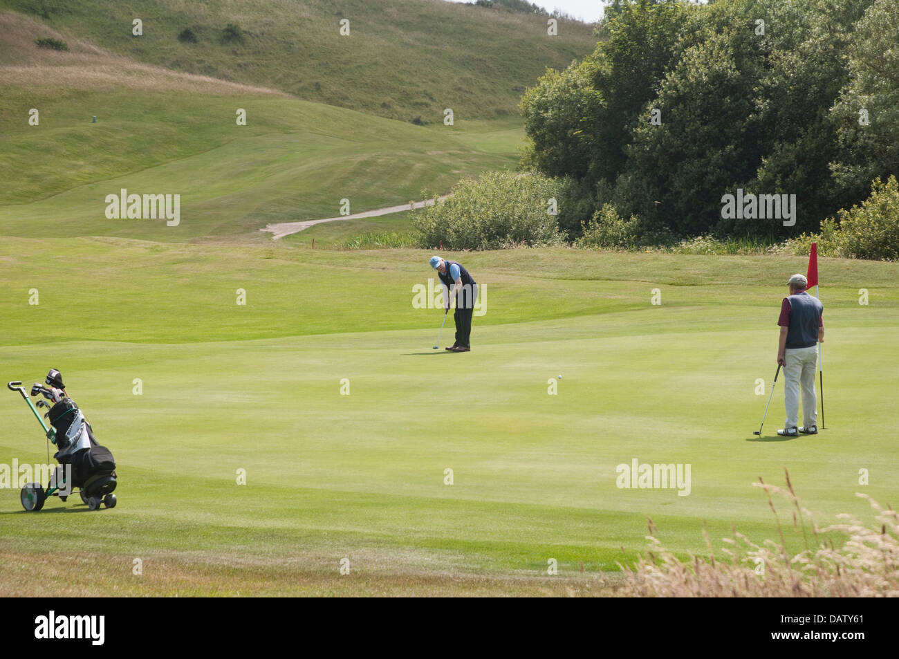 Two golfers with caddy, on a green; one has just putted, whilst the other acts as a marker. St Enodoc's Golf - Stock Image