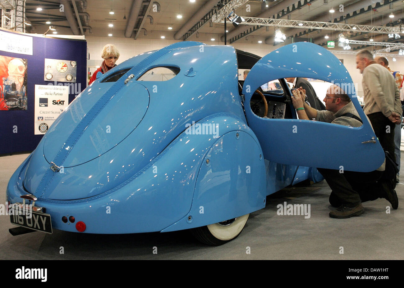 visitors of the classic motor show admire a babyblue bugatti t57