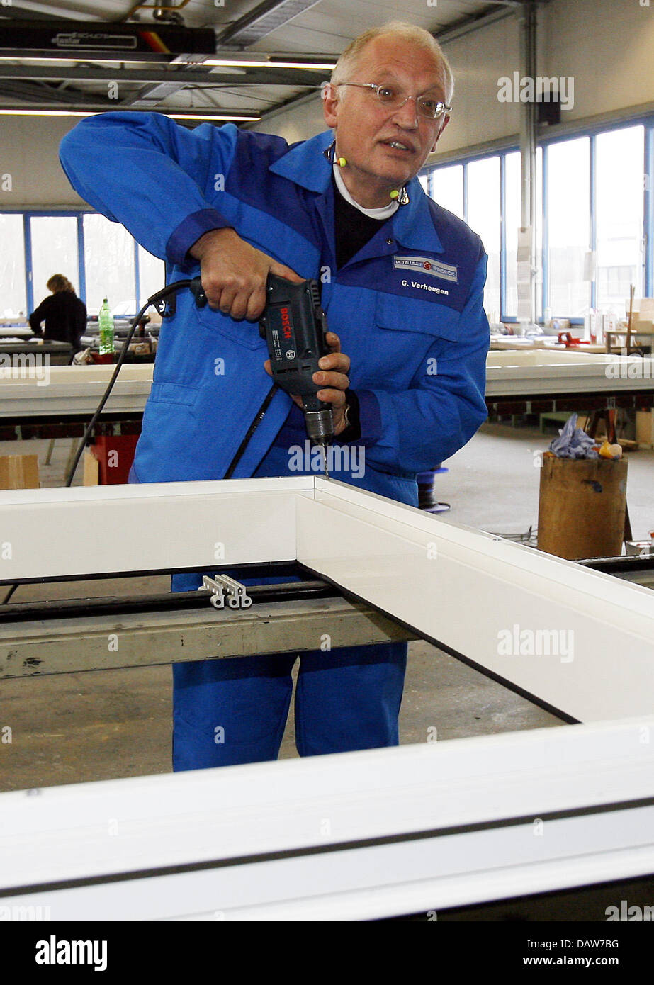 The Euopean Commissioner for Enterprise and Industry Guenter Verheugen drills holes into a window frame at the Metallbau - Stock Image
