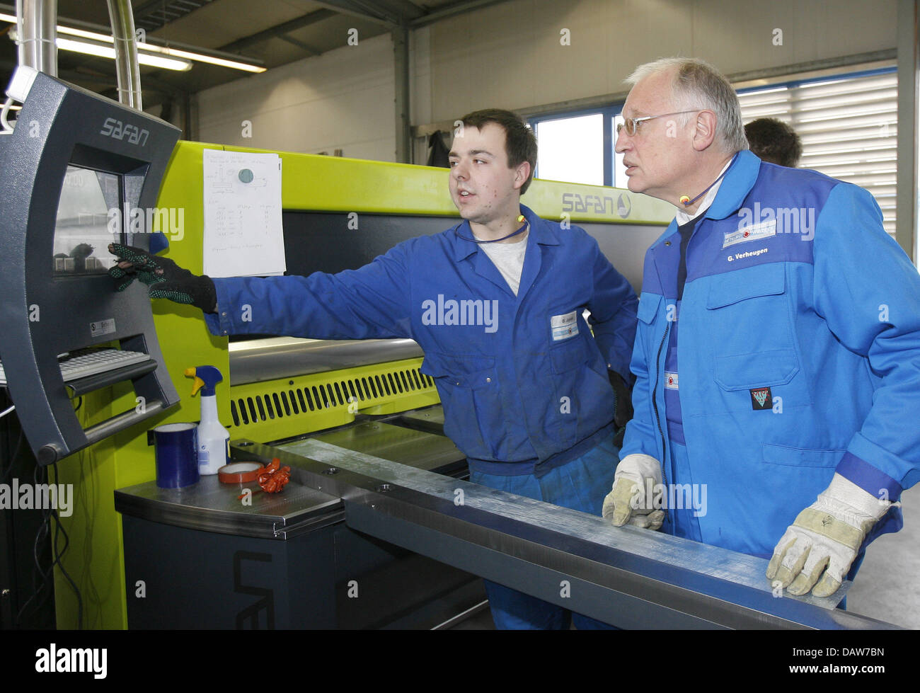Apprentice Bianco Jagielski (L) explains a sheet metal folding machine to the Euopean Commissioner for Enterprise - Stock Image