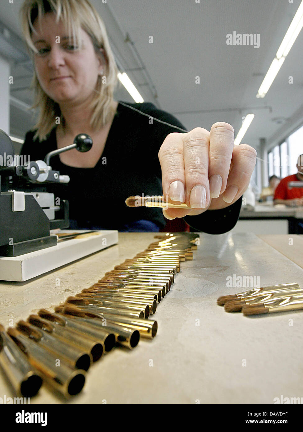 An employee puts brush parts together at the artist's brush factory Defet Gmbh in Nuremberg, Germany, 27 February Stock Photo