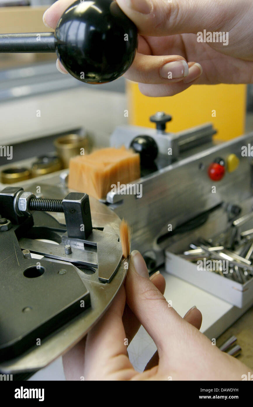 An employee assembles the parts of a brush at the artist's brush factory Defet Gmbh in Nuremberg, Germany, 27 February Stock Photo