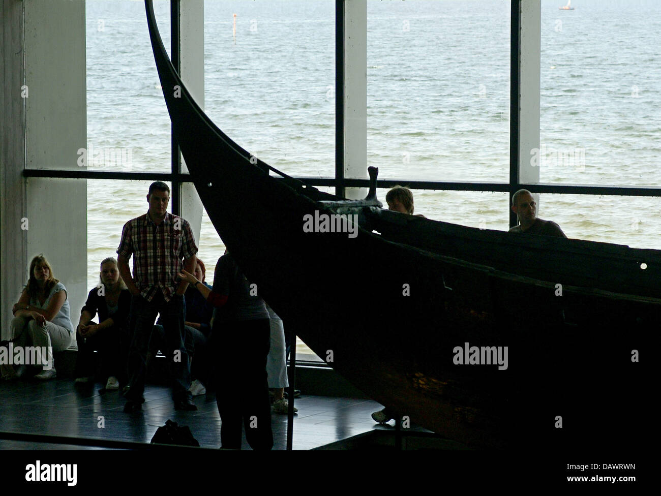Visitors take a look at a reconstructed Viking ship of the 11th century, discoverd in the Roskilde fjord in 1962, Stock Photo