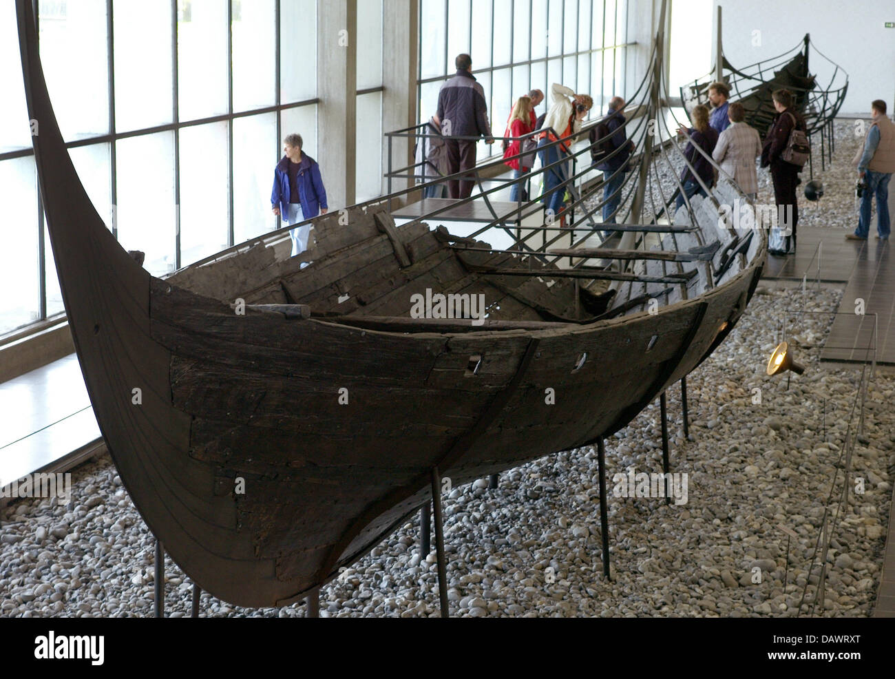 Visitors take a look at Viking ships from the 11th century, discoverd in the Roskilde fjord in 1962, in the ship Stock Photo