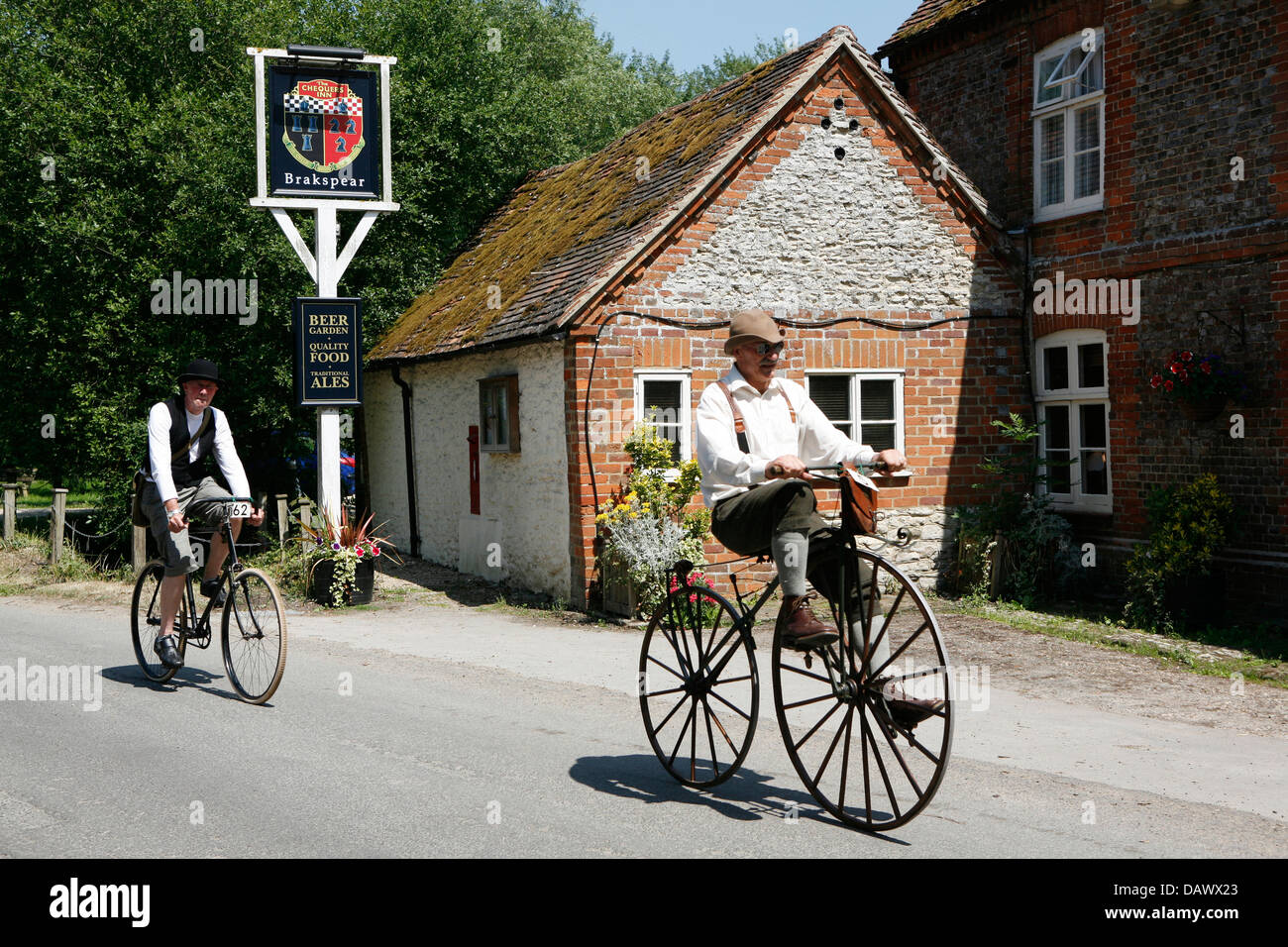 Vintage bone shaker bicycle being ridden by a man in period outfit. - Stock Image