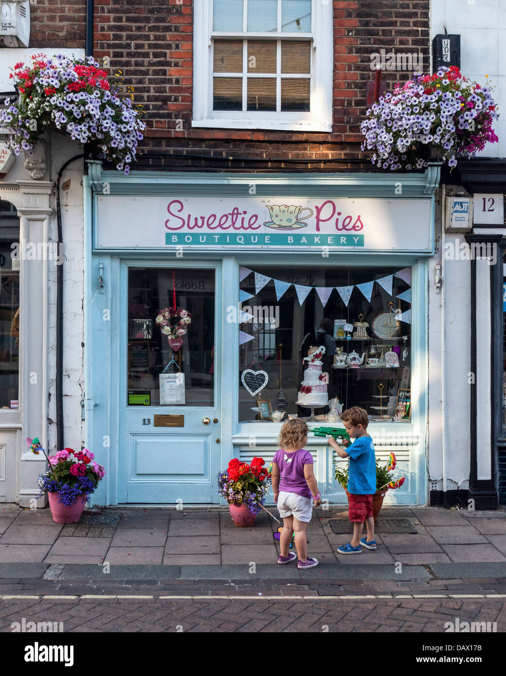 Two children play outside Sweetie Pies bakery in Church street, Twickenham, UK - Stock Image