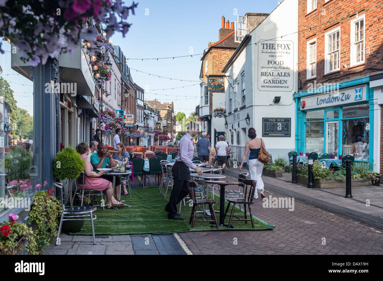 The road is closed and tables are set out for alfresco dining in summer in Church street, Twickenham, UK - Stock Image