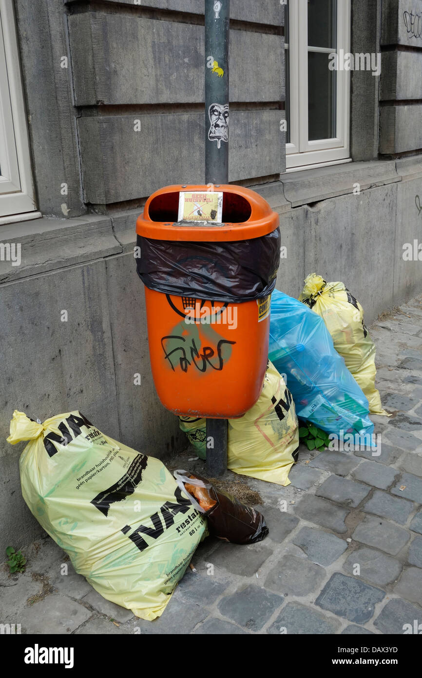 Rubbish bags / trash bag with household waste in front of house and litterbin on pavement in city street - Stock Image