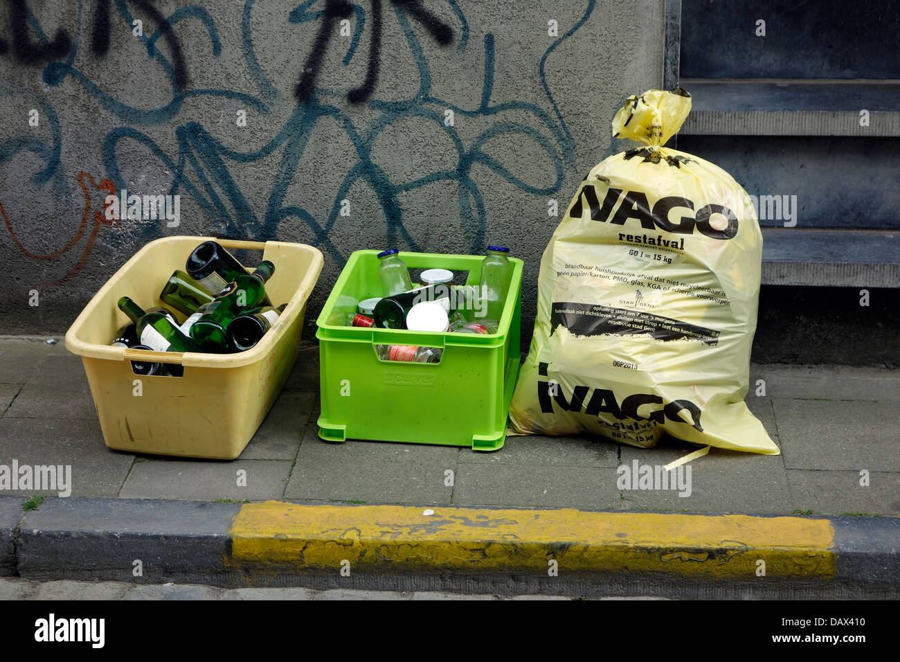 Plastic containers with glass bottles and garbage bag with household waste in front of house in city street - Stock Image