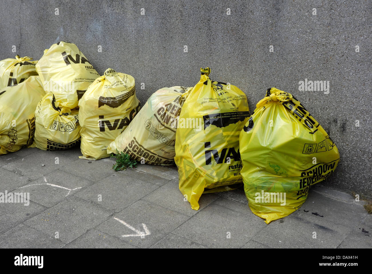Rubbish bags / trash bag with household waste on pavement in front of house in city street - Stock Image