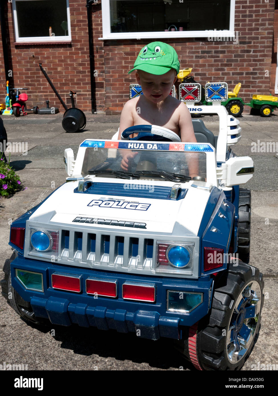 Young two year old boy in radio controlled car, England, UK. - Stock Image