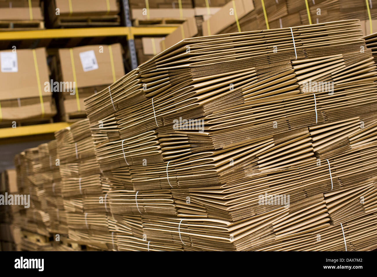 An industrial warehouse full of cardboard boxes on shelving.  - Stock Image