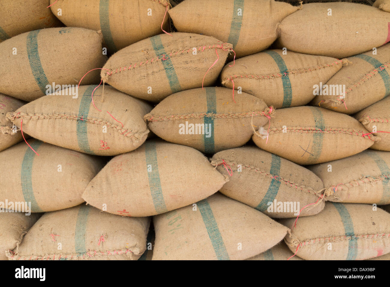 Old hemp sacks containing rice placed profoundly stacked - Stock Image