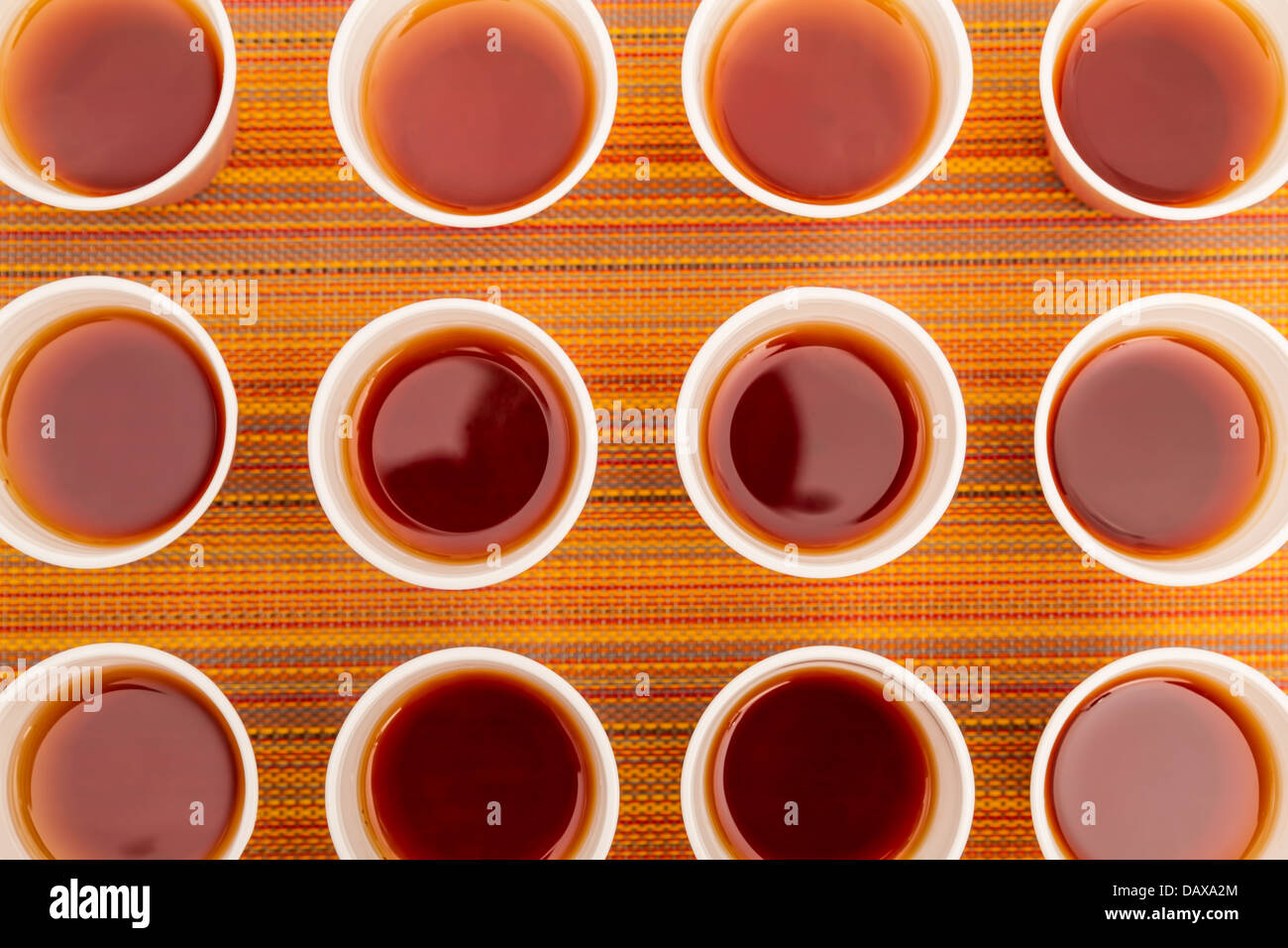 Lots of disposable cups with tea on a colorful background - Stock Image
