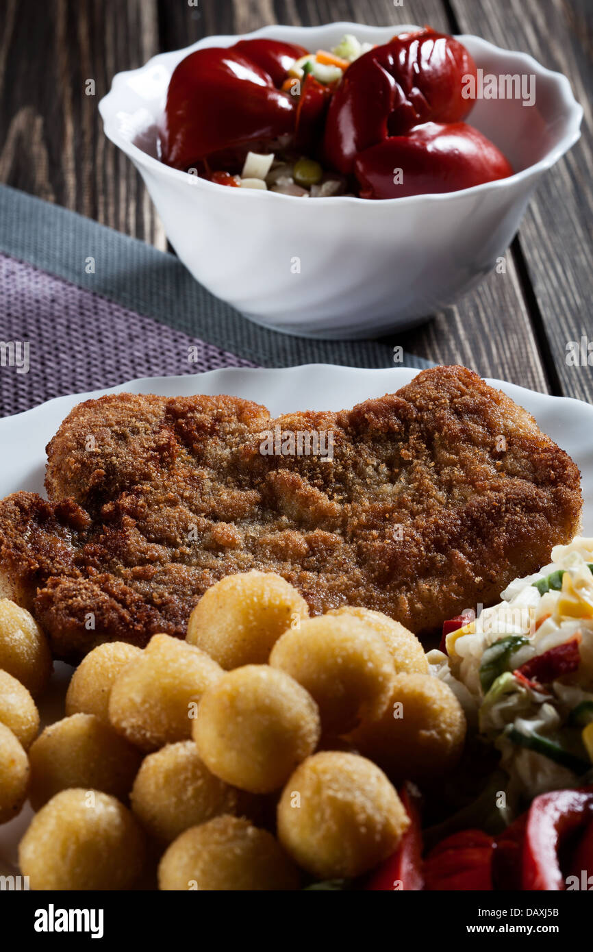 Breaded chop, prepared potatoes and salad. Mysterious light - Stock Image