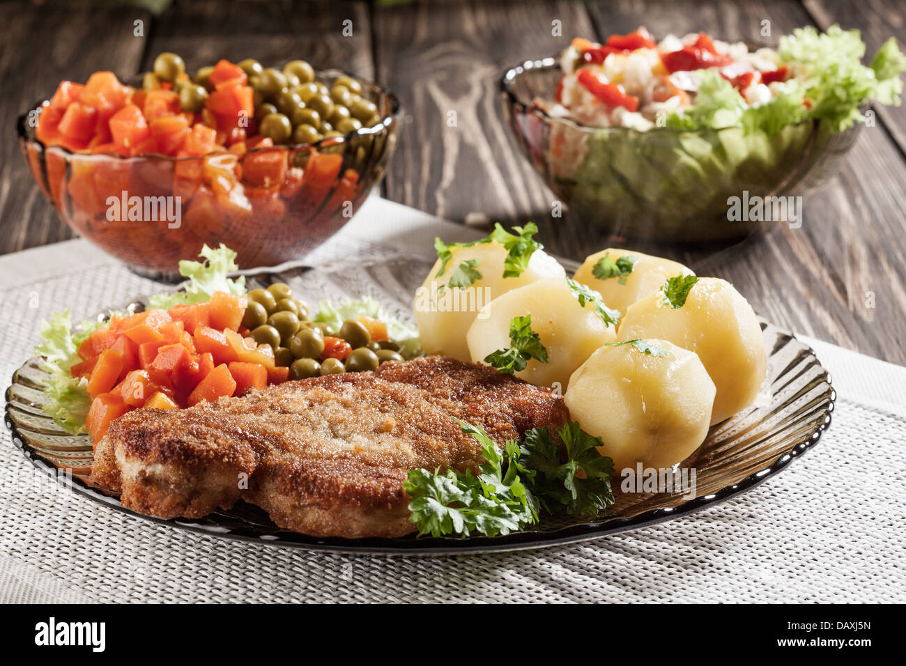Breaded chop and potatoes. Dark light. - Stock Image