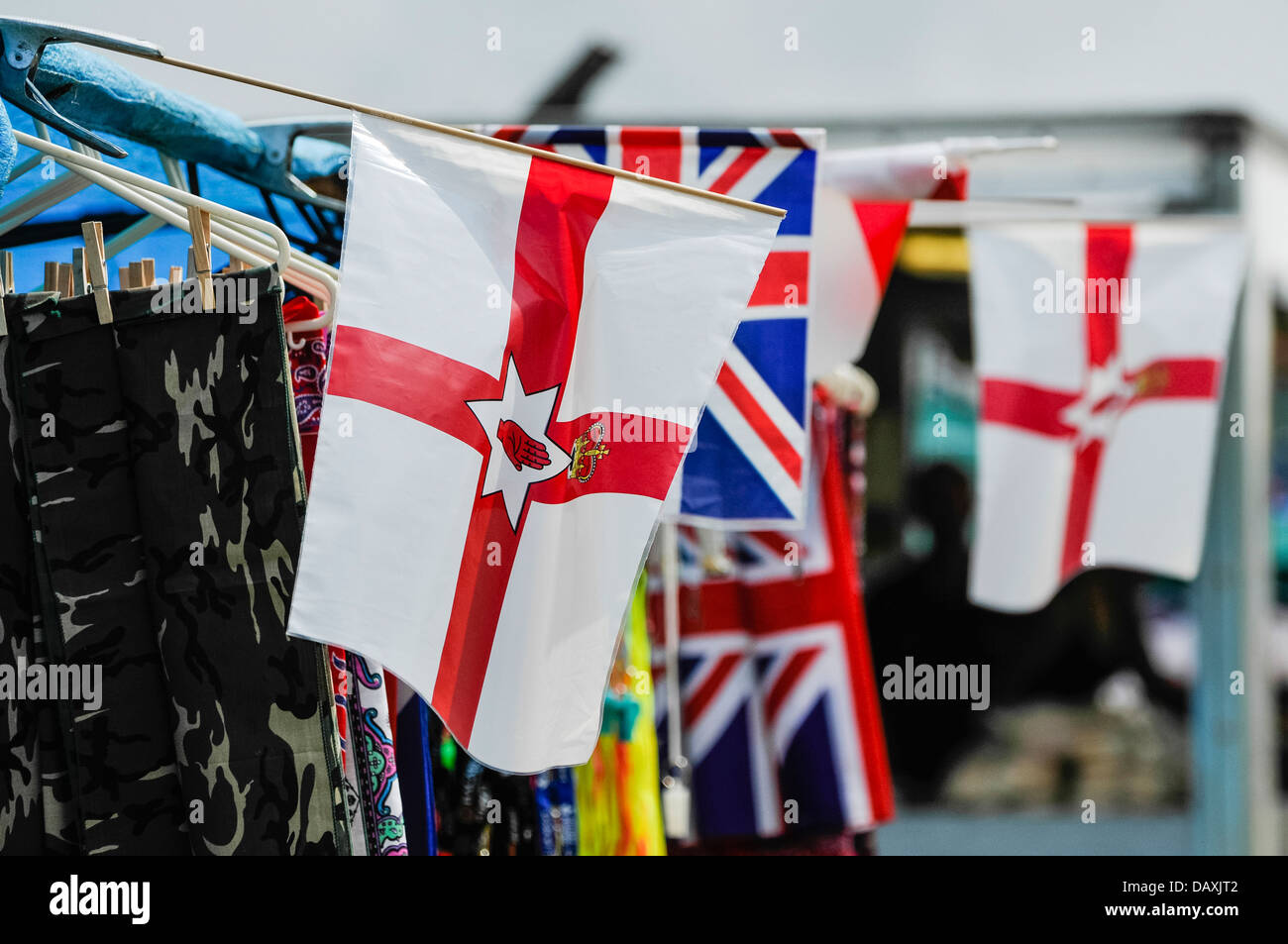 Ulster parliament (defunct) flags and Union flags on sale at a market stall - Stock Image