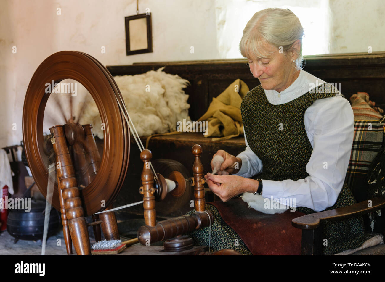 Irish woman in a cottage spinning wool - Stock Image