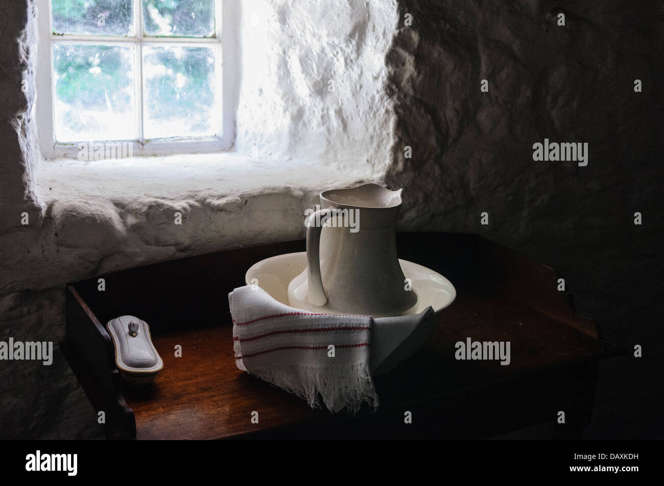 Old fashioned wash jug and basin by the window of a traditional Irish farmhouse - Stock Image