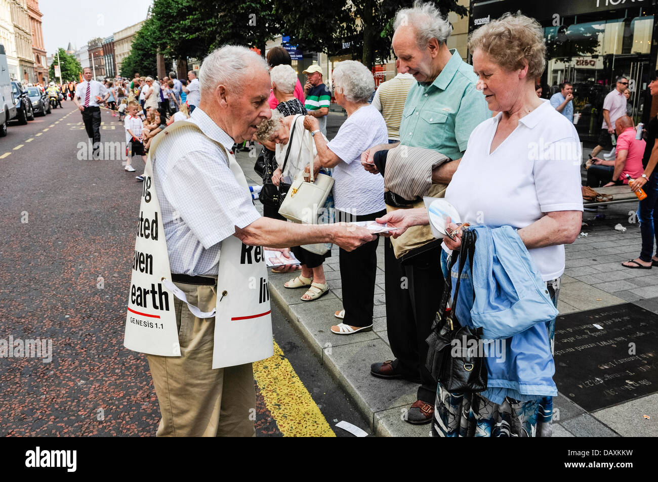 A man wearing a vest with bible verses hands out religious tracts to people in a crowd Stock Photo