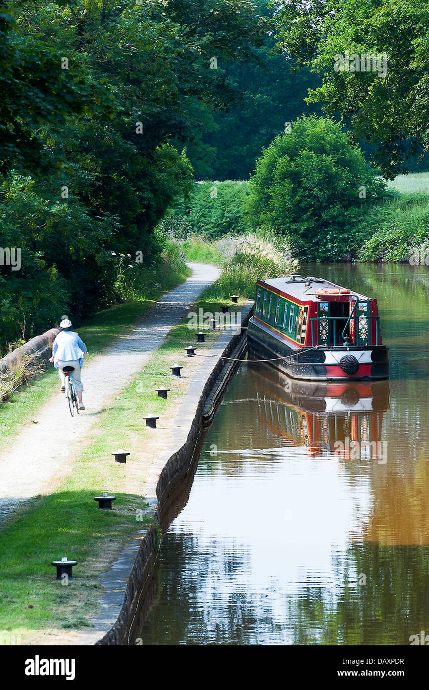 Cyclist on Towpath and Moored Narrow Boat on Trent and Mersey Canal near Rode Heath Cheshire England United Kingdom - Stock Image