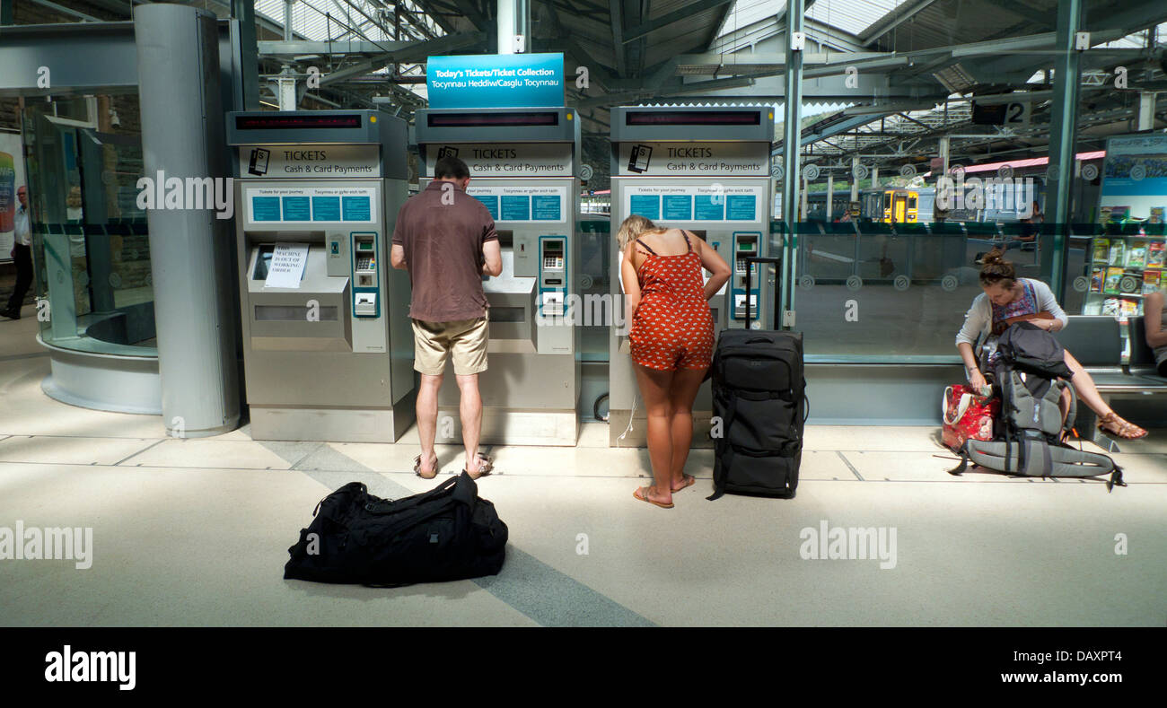 People passengers buying train tickets at automatic ticket machine on the concourse at Swansea railway station in - Stock Image