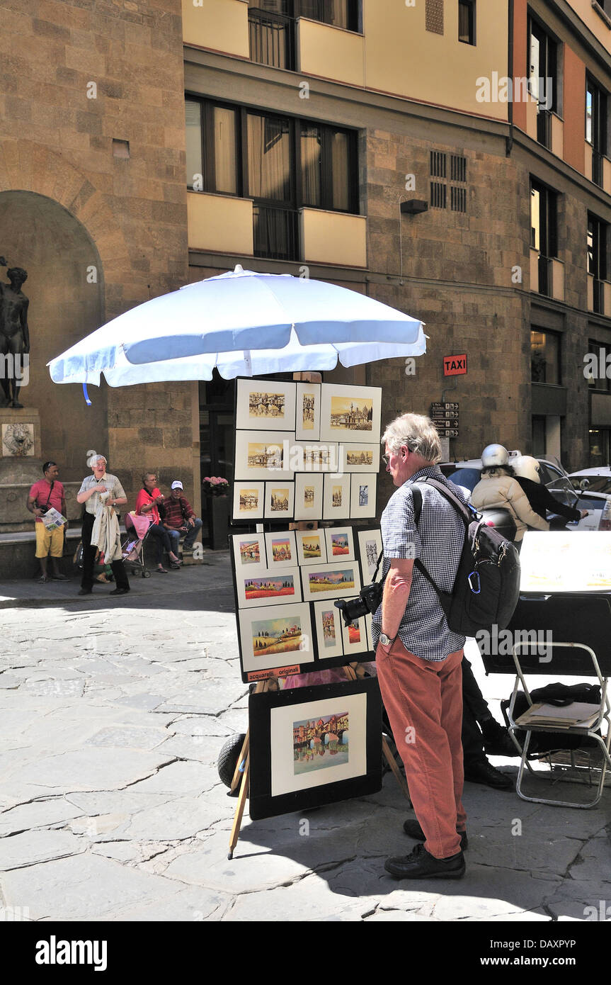 Tourist looking at an artists  display of paintings of Florence the entrance  of the  Ponte Vecchio bridge -Florence - Stock Image