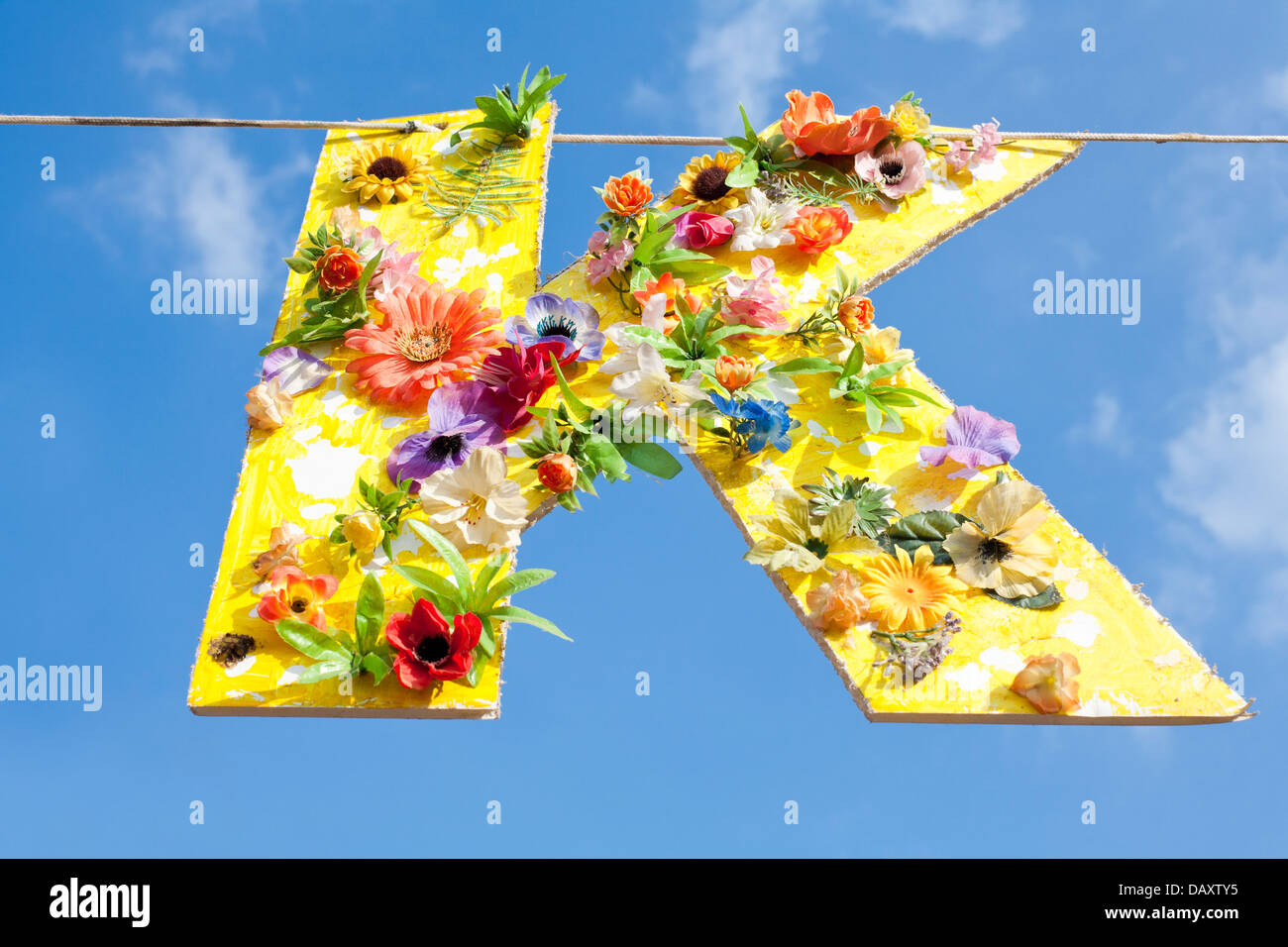 Cardboard cutout of the letter K, painted yellow and covered in flowers. Hanging on a line against a blue summer - Stock Image