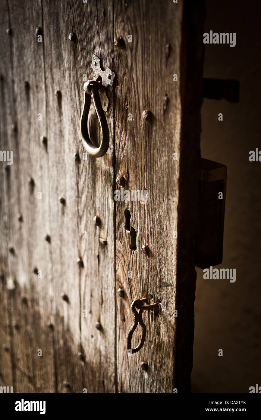 Old wooden door left ajar. Wood plank construction with metal studs, handle and catch. - Stock Image